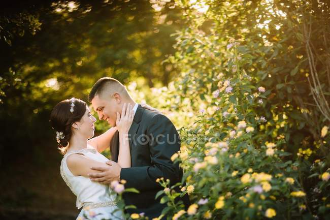 Side view of graceful tender wedding couple bonding and looking to eyes in garden — Stock Photo