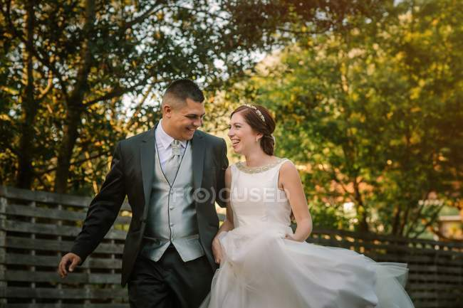 Happy just married couple running along fence in garden — Stock Photo