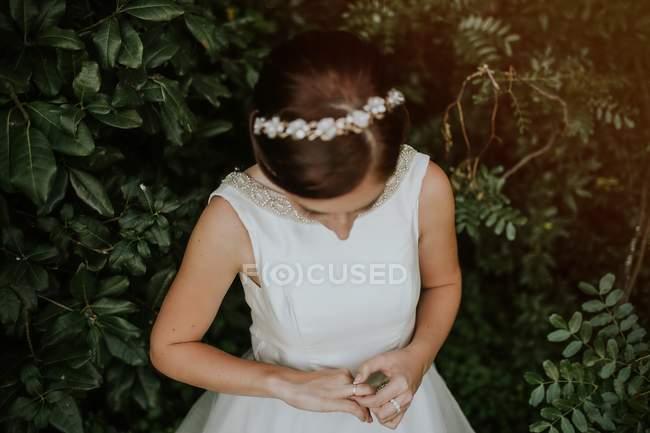 Mariée en diadème et robe élégante jouissant anneau sur doigt dans le jardin vert — Photo de stock