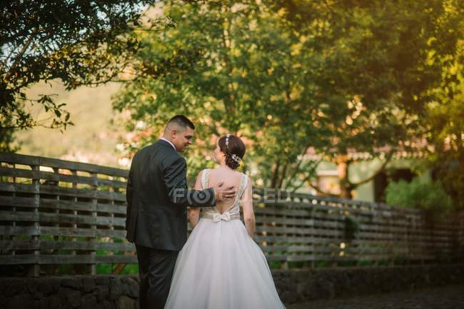 Smiling groom and bride hugging in park — Stock Photo