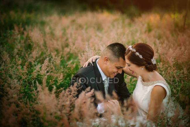 Smiling groom and bride hugging and kissing in park — Stock Photo