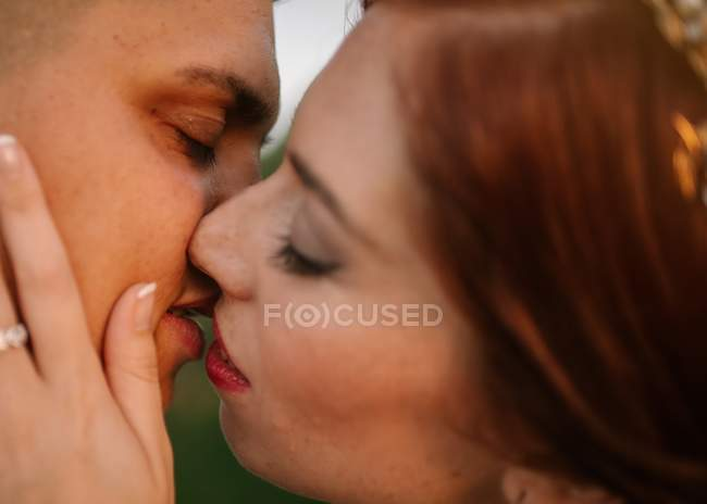 Side view of tender wedding couple with closed eyes touching face and kissing with love — Stock Photo