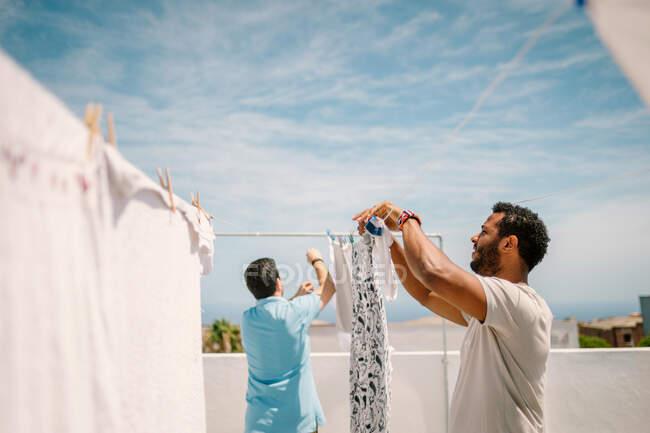 Homens multirraciais pendurando roupas em dia brilhante — Fotografia de Stock
