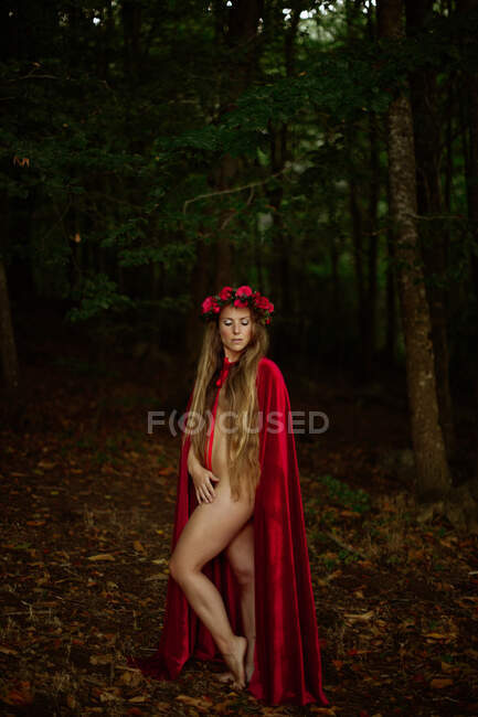 Dreamy naked woman in cape walking along dark forest — Stock Photo