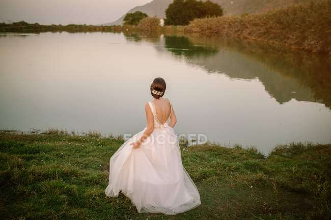 Back view of bride holding graceful dress with open back and looking at calm crystal lake reflecting sky — Stockfoto