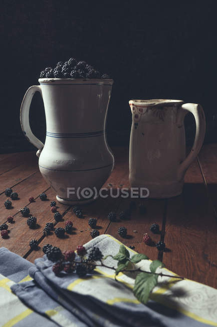 Vintage jags with ripe blackberries on wooden table and leaves on old book — Stock Photo