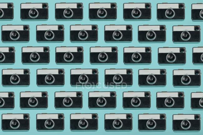 Modello senza cuciture composto da fotocamere aeree vintage disposte su sfondo blu — Foto stock
