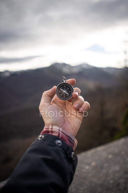 Crop man in jacket holding modern compass in outstretched hand while standing at rocky area — Stock Photo