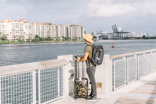 Man with suitcase and backpack, arriving on shores of Miami, watching the river and buildings on sunny morning — Stock Photo