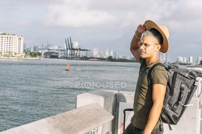 Man with a backpack rising his hat on a sunny day at the beach — Stock Photo