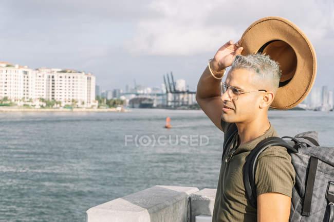 Man rising his hat and looking at beach — Stock Photo