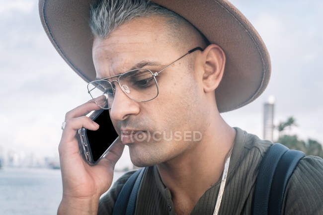 Young man with hat and talking on cellphone with worried expression — Stock Photo