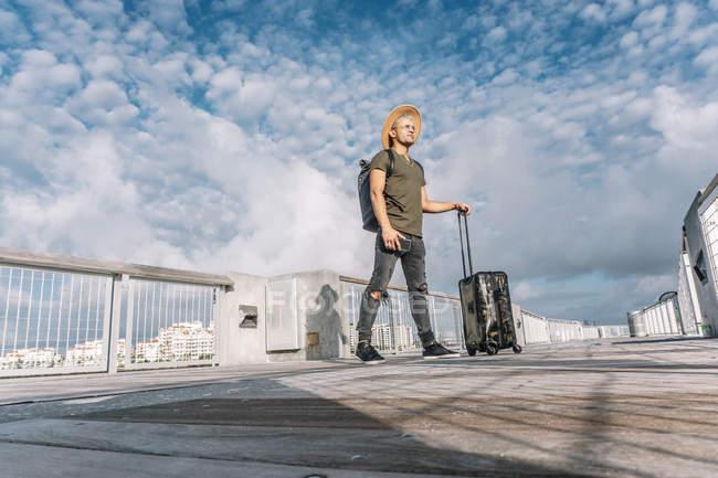 Vue latérale sur toute la longueur des bagages du touriste debout dans un chapeau brun et des jeans déchirés — Photo de stock
