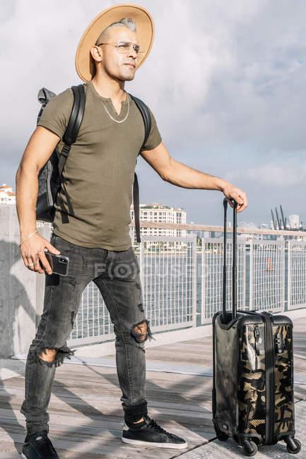 Портрет путешественника с смартфоном и чемоданом — стоковое фото