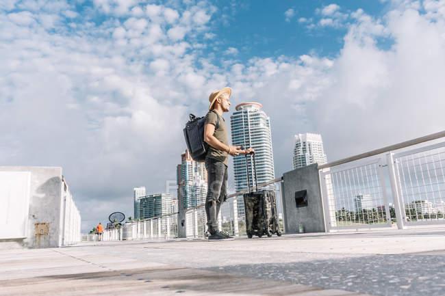 Jeune homme debout avec sa valise et profitant de la vue avant le départ — Photo de stock