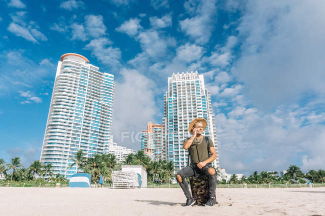 Male tourist sitting on his carrying suitcase at beach, Buildings and amazing sky view on background — Stock Photo