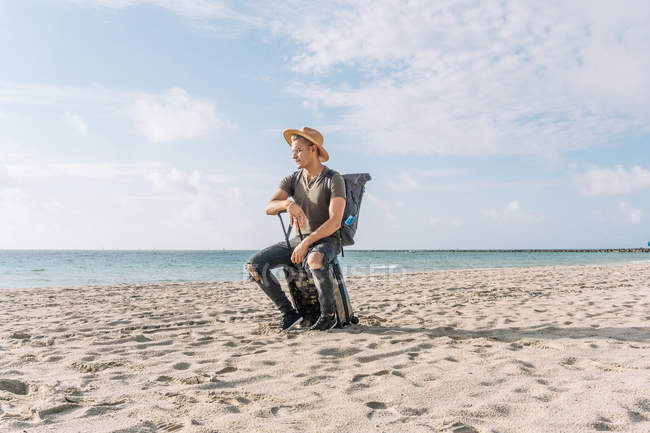 Handsome and fit guy posing with small suitcase on beach contemplating ocean — Fotografia de Stock