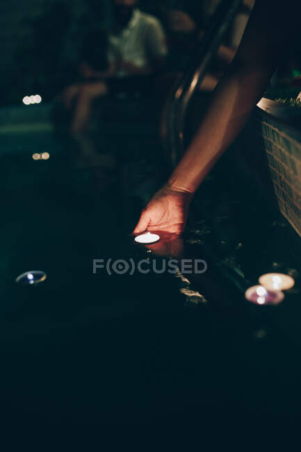 Woman swimming in pool with candles — Stock Photo