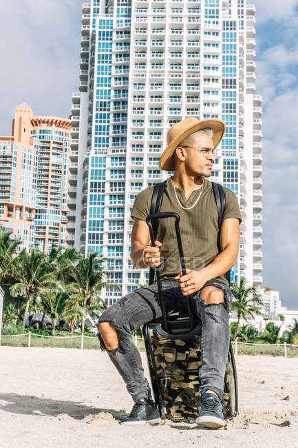 Мужчина, прибывающий на курорт на пляже, в шапке-ушанке, футболке, джинсах и закрытой обуви — стоковое фото