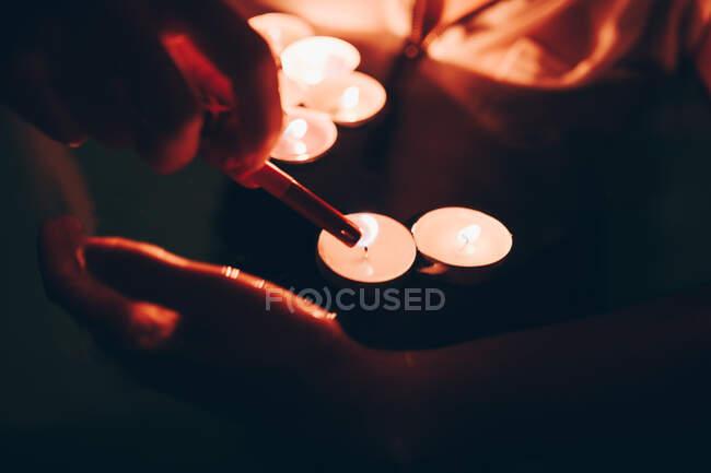 Вночі, плаваючи в басейні, одягни анонімну людину, яка запалює маленькі свічки. — стокове фото