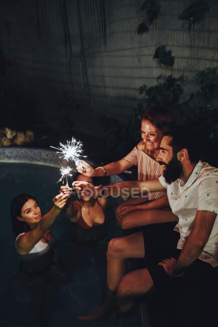 Amici allegri che bruciano scintille vicino alla piscina — Foto stock