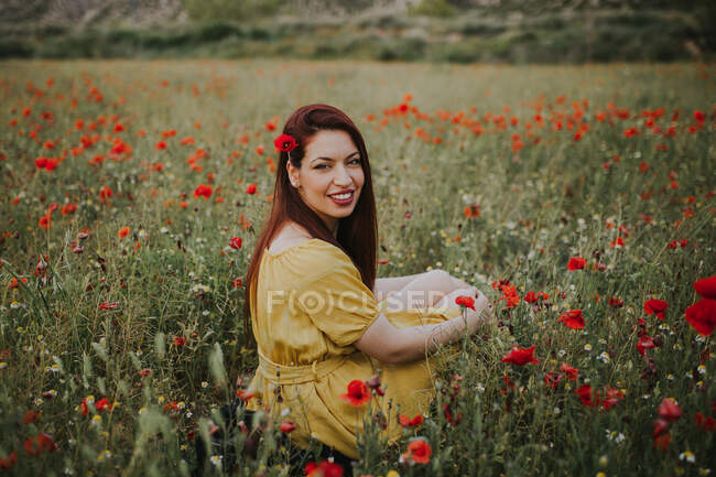 Pensive attractive red haired adult lady in yellow dress with red poppy in hair and red lips looking over shoulder at camera while sitting alone in blurred amazing green meadow with red and white flowers against hills under gray cloudy sky — Stock Photo