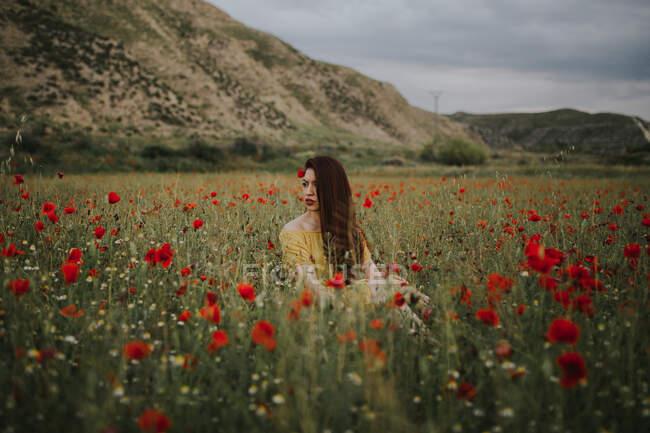 Pensoso attraente signora adulta dai capelli rossi in abito giallo con papavero rosso in capelli e labbra rosse guardando altrove mentre seduto da solo in sfocato incredibile prato verde con fiori rossi e bianchi contro le colline sotto cielo grigio nuvoloso — Foto stock