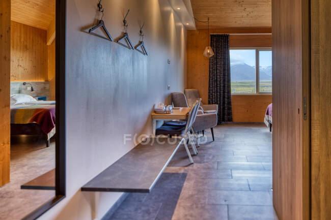 Quarto de hotel limpo e acolhedor com mobiliário confortável e grande janela com vista incrível prado verde tranquilo e montanhas nebulosas borradas — Fotografia de Stock