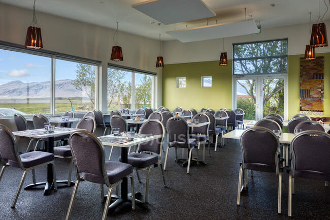 Neat empty cozy light hotel canteen with comfortable furniture on first floor near parking with windows overlooking blurred green meadow and snowy mountains — Stock Photo