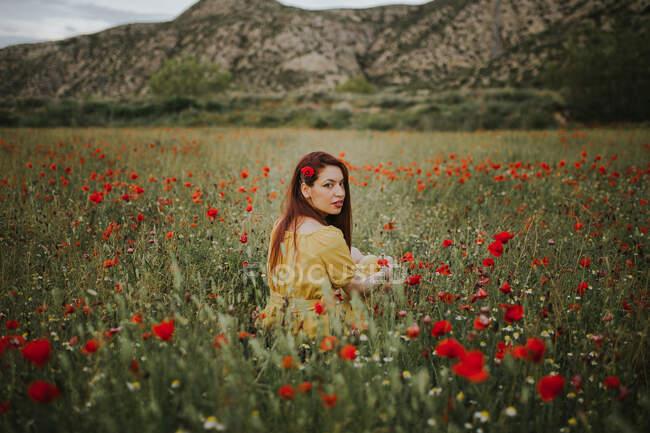 Pensoso attraente signora adulta dai capelli rossi in abito giallo con papavero rosso in capelli e labbra rosse guardando oltre la spalla alla fotocamera mentre seduto da solo in sfocato incredibile prato verde con fiori rossi e bianchi contro le colline sotto cielo grigio nuvoloso — Foto stock