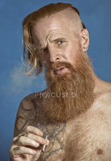 Pensivo confiante adulto de cabelos vermelhos hipster acendendo cigarro e olhando para a câmera — Fotografia de Stock