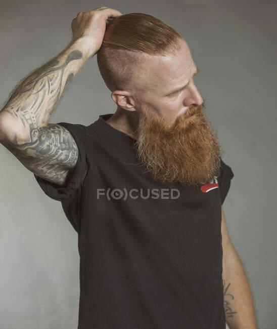 Уверенный взрослый рыжеволосый хипстер трогает волосы и отворачивается — стоковое фото