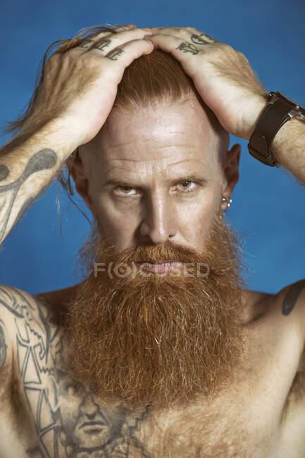 Confiante adulto de cabelos vermelhos hipster tocando o cabelo e olhando para a câmera — Fotografia de Stock