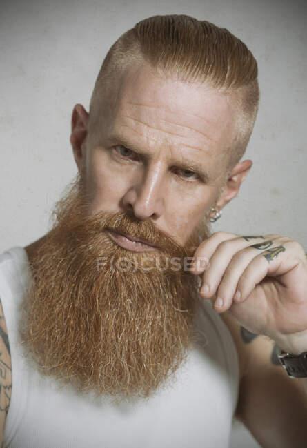 Pensativo de cabelos vermelhos barbudo homem de meia idade em singlet branco casual com tatuagem em dedos e braços e brincos no ouvido tocando bigode e olhando para a câmera contra fundo cinza — Fotografia de Stock