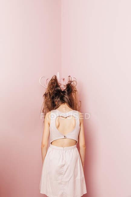 Vista concettuale da dietro di una ragazza adolescente con i capelli aggrovigliati su sfondo rosa — Foto stock