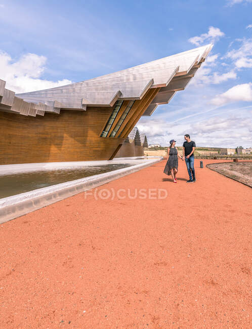Lovely couple holding hands and walking on orange road along amazing creative designed building in bright day — Stock Photo