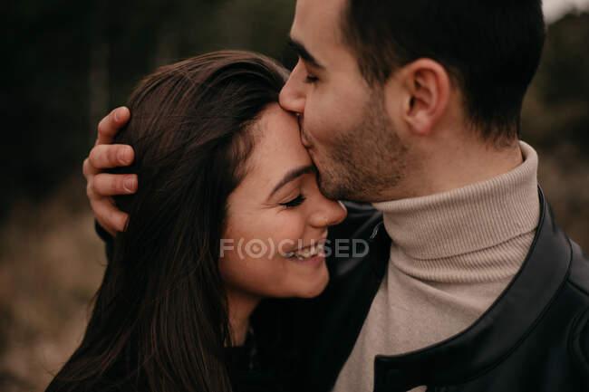Vue latérale du couple amoureux les yeux fermés, souriant tout en s'embrassant le long des conifères pendant la journée par temps venteux couvert — Photo de stock