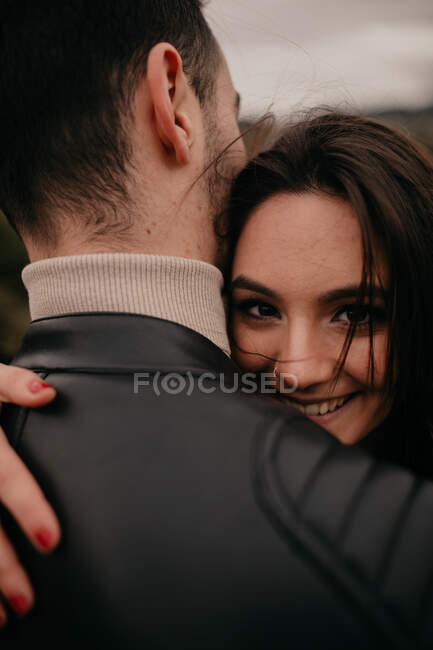 Young woman in love embracing unrecognizable boyfriend and smiling while looking at camera during daytime — Stock Photo
