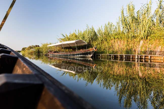 Seite des modernen Bootssegelns entlang der ländlichen Küste — Stockfoto