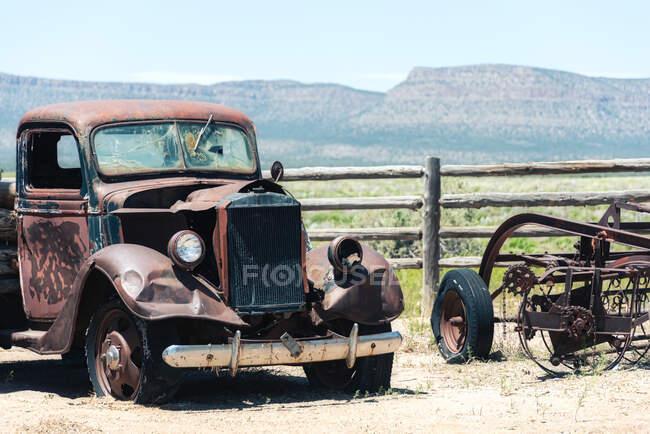 Véhicules endommagés garés par une clôture en bois dans un champ ensoleillé et des montagnes lointaines sur la Route 66, États-Unis — Photo de stock