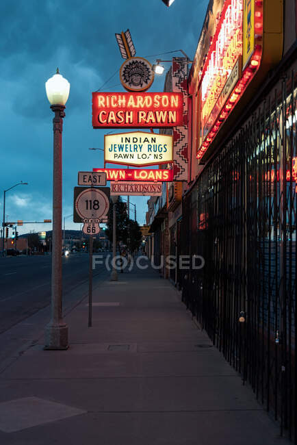 Carteles publicitarios de neón brillante de la tienda y farola en la acera oscura en Gallup, Nuevo México, EE.UU. - foto de stock