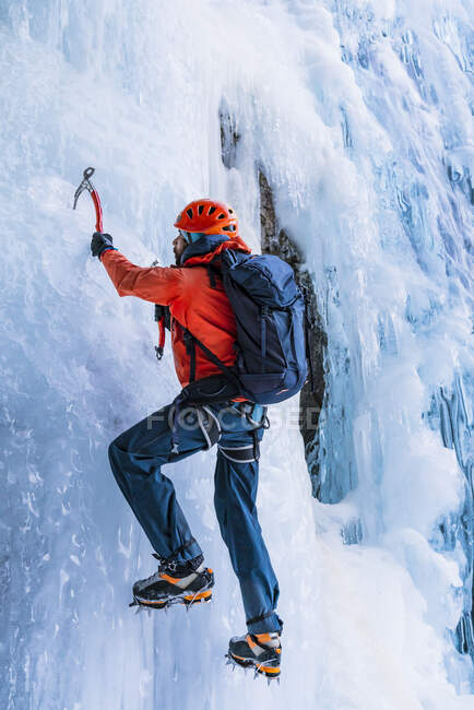 Back view of person in warm clothes with backpack using tools to climb frozen mountain glacier — Stock Photo