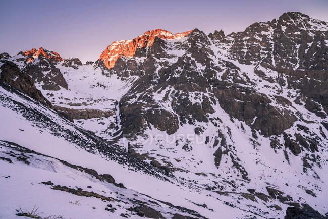 Tranquillo pendii rocciosi della catena montuosa con cime innevate alla luce del giorno — Foto stock