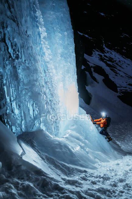Vue latérale de la personne en vêtements chauds avec sac à dos et lampe de poche à l'aide d'outils pour escalader le glacier de montagne gelé dans l'obscurité — Photo de stock