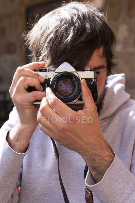 Позитивный человек в повседневной одежде с камерой регулировки оптики для фотосессии, стоя снаружи — стоковое фото