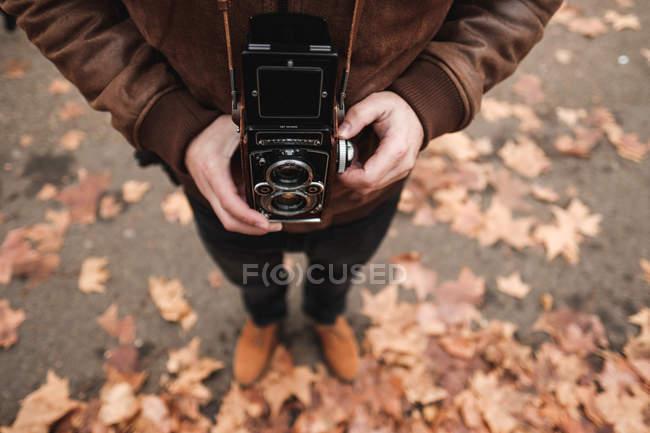 Обрезанное изображение туриста с ретро-фотокамерой, стоящего на улице Лондона — стоковое фото