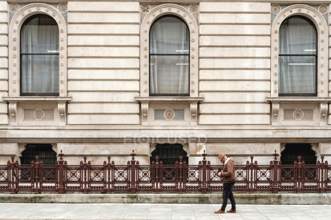 Side view of adult man with photo camera walking near fence and aged ornamental building on street of London — Stock Photo