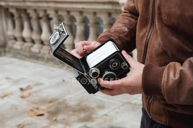 Imagen recortada de películas de cambio turístico en cámara fotográfica retro mientras se encuentra en la calle de Londres. - foto de stock