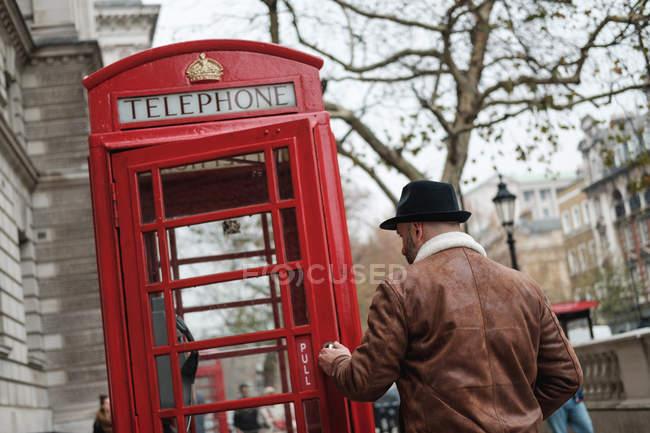 Вид сзади взрослого мужчины, идущего по телефону в красном ящике на улице Лондона — стоковое фото