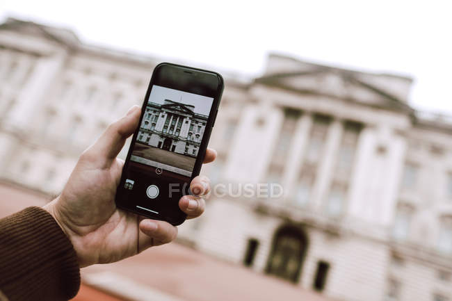 Cropped image of tourist using smartphone to take picture of aged ornamental building on street of London — Stock Photo